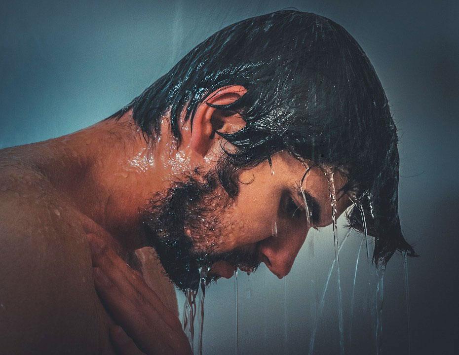 Mann mit Bart beim Duschen